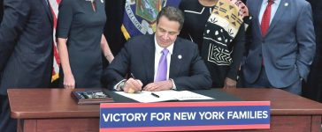 New York Gov. Andrew Cuomo (C) signs a law that will gradually raise New York's minimum wage to $15, at the Javits Convention Center, in New York, April 4, 2016. Standing, left to right, are New York state Sen. Jeffrey Klein, New York Lt. Gov. Kathy Hochul, New York state Sen. Andrea Stewart-Cousins, and New York state Assembly Speaker Carl Heastie. REUTERS/Richard Drew