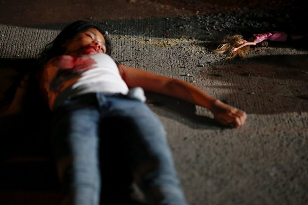 """A 17 year old girl lays dead next to her doll after she and her friend were killed by unknown motorcycle-riding gunmen, in an alley in Manila, Philippines early October 26, 2016. According to the police, a sign on a cardboard reading """"Tulak ka, hayop ka"""", which translates to """"You are a (drug) pusher, you are an animal"""" was found with the body of girl's friend. REUTERS/Damir Sagolj"""
