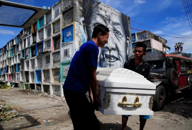 Graveyard workers carry the coffin of Eddie Languido, 56, victim of a summary execution by unknown assailants related to the drug war, during his funeral, attended by his son and friends, at the Navotas cemetery, north of Metro Manila, Philippines January 31, 2017. REUTERS/Romeo Ranoco