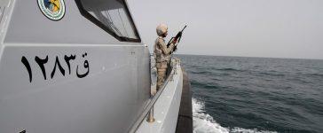 Saudi border guard watches as he stands in boat off coast of Red Sea on Saudi Arabia's maritime border with Yemen, near Jizan