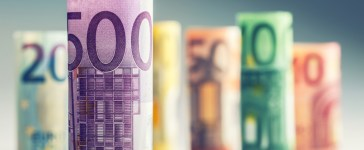 Several hundred euro banknotes stacked by value. (Shutterstock/ Marian Weyo)