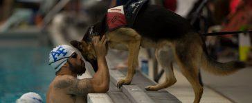 Air Force athlete August O'Niell kisses his service dog, Kai. (U.S. Air Force photo by Senior Airman Justyn M. Freeman/ Released)