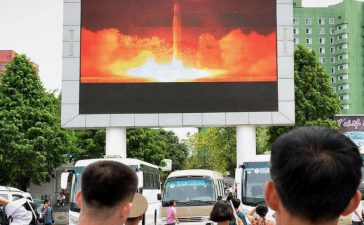 People watch news report showing North Korea's Hwasong-14 missile launch on electronic screen at Pyongyang station, North Korea in this photo taken by Kyodo on July 29, 2017. Mandatory credit Kyodo/via REUTERS