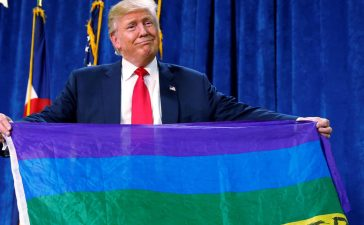"Republican presidential nominee Donald Trump holds up a rainbow flag with ""LGBTs for TRUMP"" written on it at a campaign rally in Greeley, Colorado, U.S. October 30, 2016. REUTERS/Carlo Allegri"