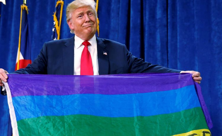 """Republican presidential nominee Donald Trump holds up a rainbow flag with """"LGBTs for TRUMP"""" written on it at a campaign rally in Greeley, Colorado, U.S. October 30, 2016. REUTERS/Carlo Allegri"""