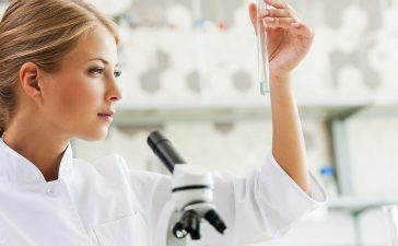 Discovering cure. Concentrated young female scientist holding test tube and looking at it while sitting at her working place (Shutterstock/g-stockstudio)