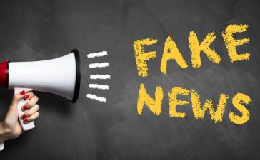 """hand with megaphone and the message """"fake news"""" (Shutterstock/fotogestoeber)"""