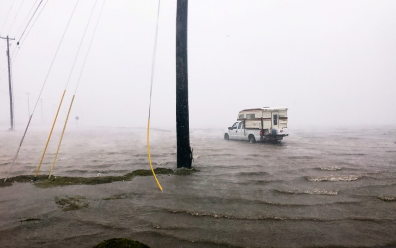 "Craig ""Cajun"" Uggen, 57, nearly floods his truck as Hurricane Harvey comes ashore in Corpus Christi, Texas. Minutes later, high winds blew off the camper carrying all of his belongings. REUTERS/Brian Thevenot"
