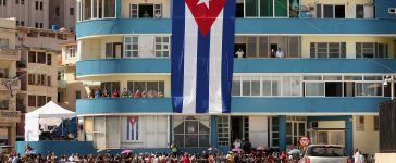 Hundreds of Cubans and visitors from other countries gather across the street from the newly reopened U.S. Embassy to observe the flag-raising ceremony August 14, 2015 in Havana, Cuba. The first American secretary of state to visit Cuba since 1945, Secretary of State John Kerry visited the reopened embassy, a symbolic act after the the two former Cold War enemies reestablished diplomatic relations in July. (Photo by Chip Somodevilla/Getty Images)