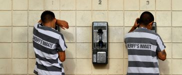Inmates serving a jail sentence make a phone call at Maricopa County's Tent City jail in Phoenix July 30, 2010. REUTERS/Joshua Lott