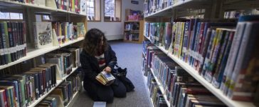 Recent refugee from Syria Sandy Khabbazeh looks at books she first used to learn to read at a library in Oakland, New Jersey, November 19, 2015. Picture taken November 19, 2015. REUTERS/Carlo Allegri - RTX1VO1V