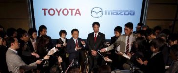 Toyota President Akio Toyoda and Mazda President and CEO Masamichi Kogai are surrounded by media as they speak after their joint news conference in Tokyo in 2015. (Reuters/Issei Kato)