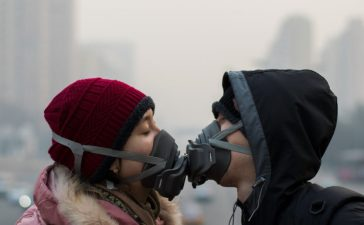 An unidentified couple try to kiss during air pollution in Beijing. Air pollution is a serious problem in Beijing. (Shutterstock/Nahorski Pavel)