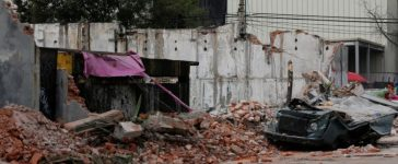 A damaged wall and a smashed vehicle are pictured after an earthquake in Mexico City