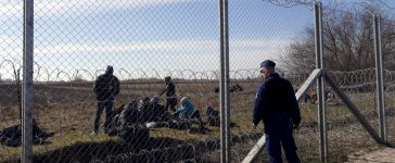 Migrants rest as a policeman watches them near the border fence near Morahalom, Hungary, February 22, 2016. REUTERS/Laszlo Balogh