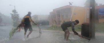 People pick up debris as Hurricane Irma howled past Puerto Rico after thrashing several smaller Caribbean islands, in Fajardo, Puerto Rico September 6, 2017. REUTERS/Alvin Baez