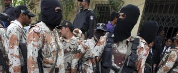 Pakistan Rangers stand guard near some men, who were detained during a raid on the Muttahida Qaumi Movement (MQM) political party headquarters, to present them before an anti-terrorism court in Karachi