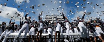 Graduates of the United States Military Academy toss their hats into the air at the conclusion of commencement ceremonies in West Point