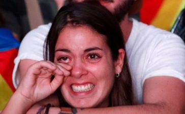 A woman reacts as she watches a session of the Catalonian regional parliament on a giant screen at a pro-independence rally in Barcelona, Spain, October 10, 2017. REUTERS/Gonzalo Fuentes