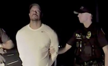 Tiger Woods is seen handcuffed and searched by police officers in this still image from police dashcam video in Jupiter, Florida, U.S. on May 29, 2017. Video released on May 31, 2017. Courtesy Jupiter Police Department/Handout via REUTERS