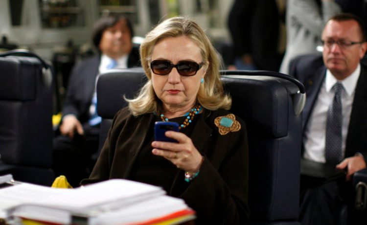 Former Secretary of State Hillary Clinton checks her PDA, Libya October 18, 2011. REUTERS/Kevin Lamarque