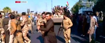 Kurdish forces on an armoured vehicle drive in the street of Kirkuk
