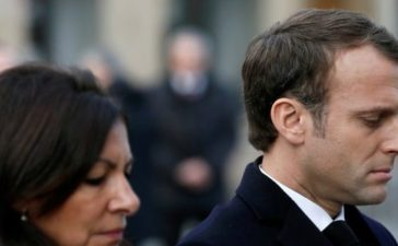 French President Emmanuel Macron (R) and Mayor of Paris Anne Hidalgo (L) attend a minute of silence as they stand in front of a commemorative plaque facing the 'Le Carillon' bar and 'Le Petit Cambodge' restaurant during a ceremony marking the second anniversary of the Paris attacks of November 2015 in which 130 people were killed, in Paris, France, November 13, 2017. REUTERS/Etienne Laurent/Pool