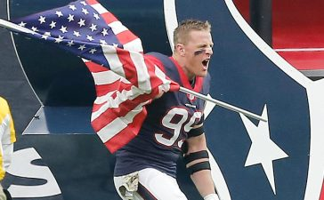 J.J. Watt of the Houston Texans runs out with the American flag before playing against the New York Jets in November 2015 in Houston. (Photo by Thomas B. Shea/Getty Images)