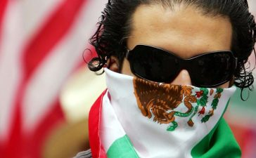 LOS ANGELES, CA - APRIL 15: A man keeps his face covered with a Mexican flag as students and supporters march to call for amnesty for illegal immigrants on April 15, 2006 in Los Angeles, California. The 3,000 people who marched through downtown to City Hall particularly oppose House bill HR 4437 by Rep. F. James Sensenbrenner, R-Wisconsin that would increase penalties for immigrant smuggling, beef up penalties for undocumented immigrants who re-enter the United States, and require employers to report Social Security numbers to the Department of Homeland Security. The march is dedicated to Ontario, California student Anthony Soltero, 14, who committed suicide on March 30 after a school administrator allegedly told him he would be fined and jailed for participating in a student walkout in support of undocumented immigrants rights on March 28. (Photo by David McNew/Getty Images)