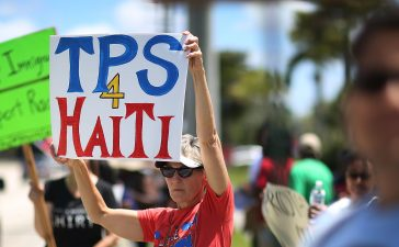 Vicki Rosenthal and others protest in front of the United States Citizenship and Immigration Services office in Broward county to urge the Department of Homeland Security to extend Temporary Protected Status for Haitian immigrants on May 21, 2017 in Fort Lauderdale, Florida. Haitians have been eligible for TPS and now the Trump Administration has until May 23 to make a decision on extending TPS for Haitians or allowing it to expire on July 22, which would mean possible deportation for the current TPS holders. (Photo by Joe Raedle/Getty Images)