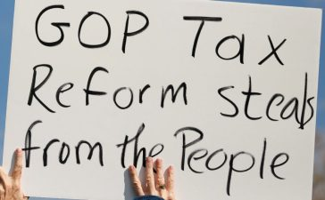 A demonstrator holds a sign during a rally against the Republican tax bill on Capitol Hill in Washington, U.S., November 15, 2017. REUTERS/Aaron P. Bernstein