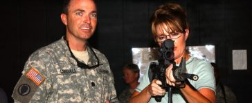 Lt. Col. David Cogdell helps Alaska Governor Sarah Palin test out the Engagement Skills Trainer at Camp Buehring, Kuwait, July 24. Palin visited the Soldiers of 3rd Battalion, 297th Infantry Regiment, Alaska National Guard to learn about their mission in Kuwait. (Department of Defense/DVIDSHub/ Spc. Christopher Gramme)