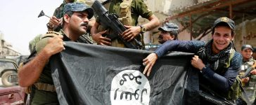 Iraqi Federal Police members hold an Islamic State flag, which they pulled down during fighting between Iraqi forces and Islamic State militants, in the Old City of Mosul