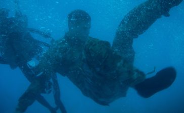A U.S. Army Soldier assigned to the 7th Special Forces Group frees himself from a parachute harness Oct. 16th in the Eglin Air Force Base Pool as part of a Combat Water Survival Test and in preparation for a deliberate parachute jump into water. The CWST is used to assess a Soldier's swimming capability and train him for maritime operations. (U.S. Army photo by Capt. Thomas Cieslak)
