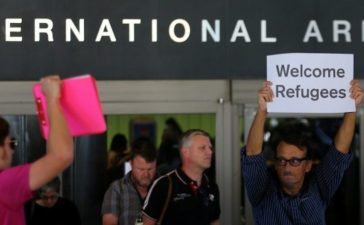 "FILE PHOTO: Retired engineer John Wider, 59, is greeted by a supporter of U.S. President Donald Trump as he holds up a sign reading ""Welcome Refugees"" at the international arrivals terminal at Los Angeles International Airport in Los Angeles, California, U.S. on June 29, 2017. REUTERS/Mike Blake/File Photo"