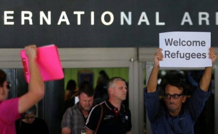 """FILE PHOTO: Retired engineer John Wider, 59, is greeted by a supporter of U.S. President Donald Trump as he holds up a sign reading """"Welcome Refugees"""" at the international arrivals terminal at Los Angeles International Airport in Los Angeles, California, U.S. on June 29, 2017. REUTERS/Mike Blake/File Photo"""