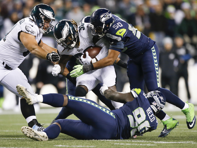 Running back Jay Ajayi #36 of the Philadelphia Eagles is tackled by defensive tackle Jarran Reed #90 of the Seattle Seahawks and K.J. Wright #50 at CenturyLink Field on December 3, 2017 in Seattle. (Photo by Otto Greule Jr /Getty Images)