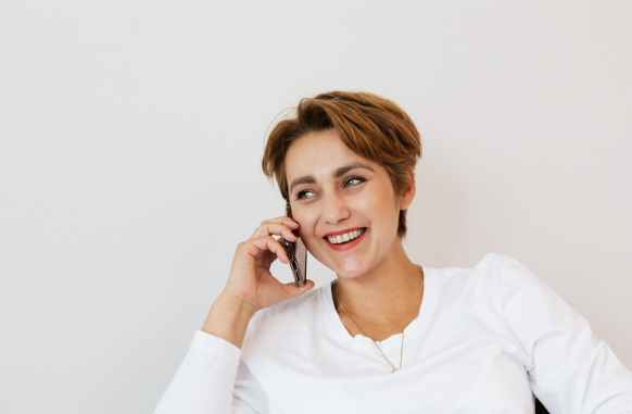 happy woman speaking on smartphone and smiling