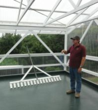 Arianna Farms manager Kraig Lee shows off a custom rake he built to dry coffee on the farm's drying porch.
