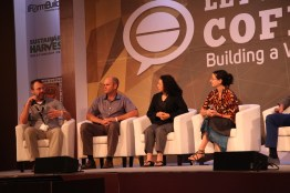 """Photo of a Friday morning plenary sessions titled """"Geisha Panel: The Famed Bean, Ten Years On."""" Hanna Neuschwander (pictured left) moderated this panel that featured Willem Boot of Boot Coffee, Ted Stachura of Equator Coffees & Teas, Maria Ruiz of Casa Ruiz SA, Aaron Davis of Roya Botanic Gardens, Kew, Ric Rhinehart of the SCAA, and Daniel Peterson of Hacienda La Esmeralda. Seated in the photo are Ted at the far right with the mic, Daniel middle left, Maria middle right, and Hanna far right."""
