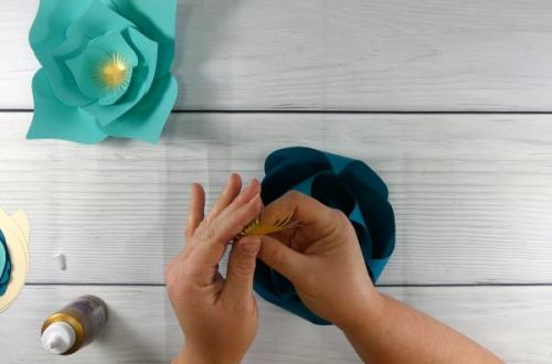 Curl up the stamen of the flower and glue it to the center of the teal paper flower