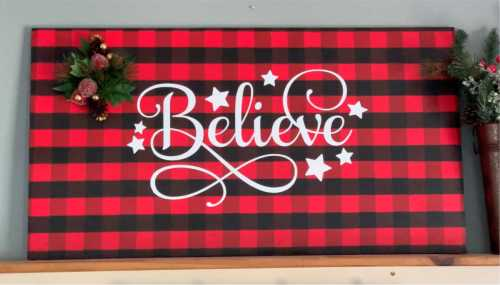 Finished Christmas sign with a painted buffalo plaid base and a vinyl believe decal