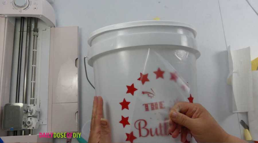 remove the transfer tape from the vinyl decal on the camp bucket