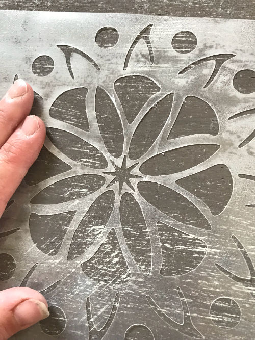 Use spray adhesive to stick your reusable stencil to your projects