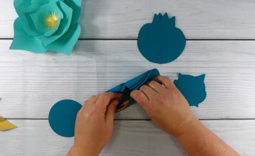 curling paper flower petals with a pencil for a paper flower display