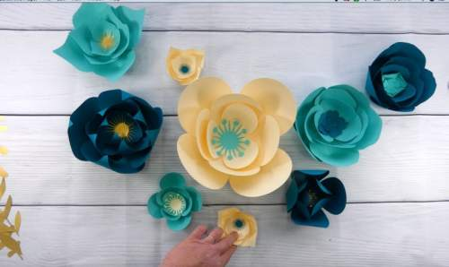 Arranging flowers for a paper flower wall back drop