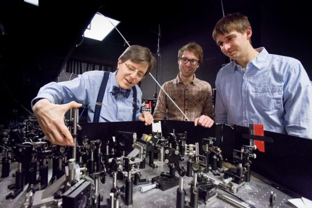 Physics+Professor+Paul+Kwiat+%28left%29+working+with+graduate+students+in+the+lab+at+Loomis+Laboratory+of+Physics.+Kwiat+is+working+on+improving+quantum+computing.+