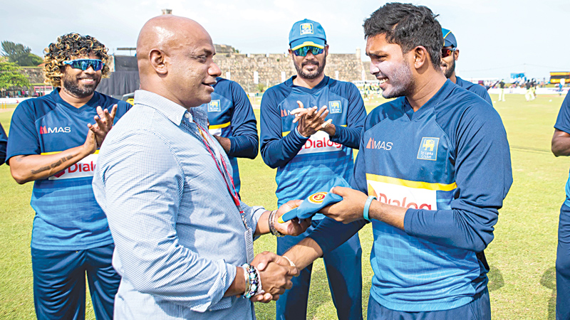 NEW CAP: Wanindu Hasaranga receives his Sri Lanka ODI cap from chief selector Sanath Jayasuriya prior to the commencement of the second ODI against Zimbabwe at the Galle International Stadium yesterday.