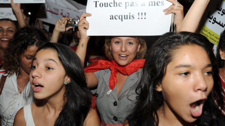 """Tunisian demonstrators shout slogans and one holds a poster reading, """"don't touch my rights"""" during a protest calling for the respect of women's rights and other fundemental rights on 13 August in Tunis AFP PHOTO / FETHI BELAID"""
