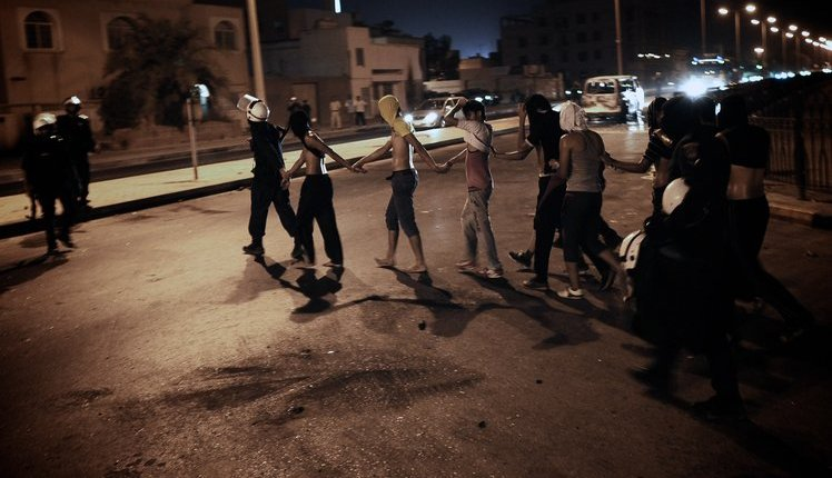Bahraini policemen arrest protestors during an anti-government demonstration in the village of Bani Jamrah, West of Manama, on August 2, 2012. AFP PHOTO/MOHAMMED AL-SHAIKH